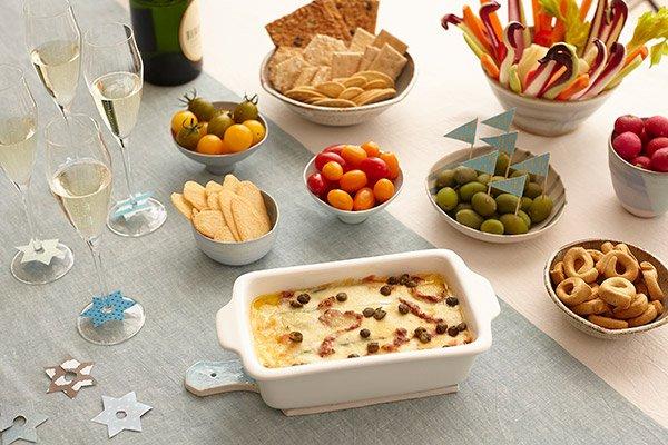 Tavola imbandita per una cena tra amici con verdure, vino, olive e Millefoglie di zucchine con la crema di Formaggio GranMix Classico e pomodori secchi